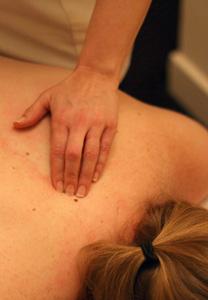 An osteopath massaging a back